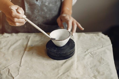 Colored slip being painted on pottery